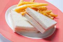 Sandwich with ham, cheese and golden French fries potatoes. On a plate Stock Photo