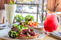 A sandwich with ham cheese and herbs on a white plate, on a wooden table, a cocktail and juice. Side view Stock Photo