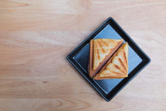 Sandwich. Ham cheese toast in black rectangle disk on the plywood tabe Royalty Free Stock Photo