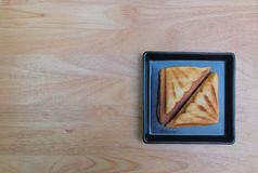 Sandwich. Ham cheese toast in black square disk on the plywood tabe Stock Images