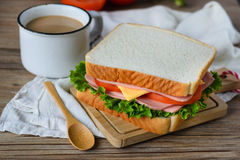 Sandwich with ham, cheese and vegetables on wood table Royalty Free Stock Images