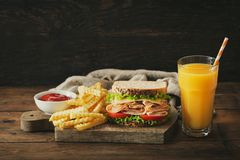 Sandwich with ham, french fries and glass of orange juice stock image
