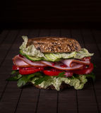 Sandwich with ham, greens, tomatoes, bread with grains on the wo Stock Photo