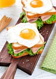 Sandwich with ham, lettuce and a fried egg. Breakfast. Royalty Free Stock Photography