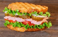Sandwich with ham, lettuce and tomatoes. On an old table Stock Photo