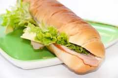 Sandwich with ham and letuce on the green plate.  Royalty Free Stock Image