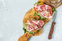 Sandwich with ham, olives, rye bread and vegetables Stock Photo
