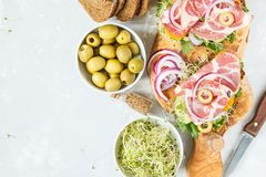 Sandwich with ham, olives, rye bread and vegetables. On a wooden board Royalty Free Stock Images