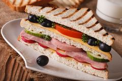 Sandwich with ham on a plate and milk. Horizontal closeup Royalty Free Stock Photography