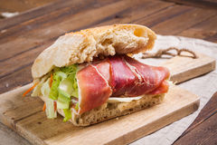 Sandwich with ham and salad on cutting board Royalty Free Stock Image