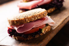 Sandwich with ham salad tomato on cutting board macro angled Stock Photos