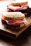 Sandwich with ham salad tomato on cutting board macro Stock Photo