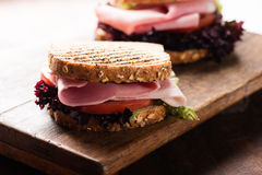 Sandwich with ham salad tomato on cutting board Royalty Free Stock Images
