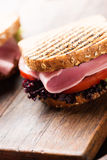 Sandwich with ham salad tomato on wooden cutting board Stock Photo