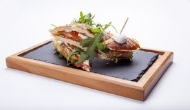 Sandwich with ham,tomato, cucumber and arugula on the wooden cut. Ting board Stock Photography