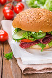 Sandwich with ham and vegetables. On wooden background Royalty Free Stock Photography
