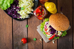 Sandwich hamburger with juicy burgers, cheese and mix of cabbage. Royalty Free Stock Photography