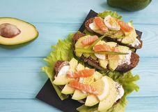 Sandwich  healthy avocado red fish egg  lunch lemon gourmet blue wooden appetizer rustic. Sandwich  avocado healthy  lemon red fish rustic on blue wooden Royalty Free Stock Photos