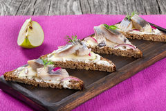 Sandwich with herring fillets, onion, pickled cucumber and dill Stock Images