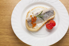 Sandwich with herring fish and caviar on bread, cherry tomato Stock Photography