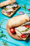 Sandwich with herring and onion on blue wooden table Stock Photography