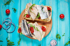 Sandwich with herring and onion on blue wooden table Royalty Free Stock Images
