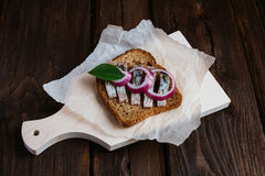 Sandwich with herring. Red onion, rye bread on a brown table Stock Images