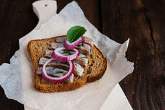 Sandwich with herring. Red onion, rye bread on a brown table Royalty Free Stock Photos