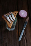 Sandwich with herring and vodka. Sandwich with herring, red onion, rye bread on a brown table Royalty Free Stock Images