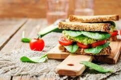 Sandwich heurté à seigle grillé par tomate d'épinards d'avocat Photos stock