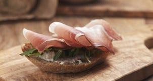 Sandwich with italian speck, arugula and cream cheese Stock Photo