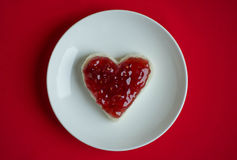 Sandwich with jam. Small sandwich with heart shaped raspberry jam stock images