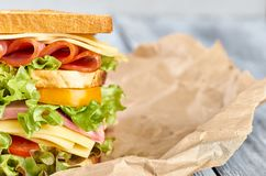 Sandwich,kraft paper sandwich. Sandwich with cheese, meat, vegetables, greens, salad, on kraft paper on wooden background stock photo