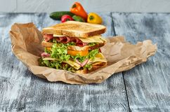 Sandwich,kraft paper sandwich. Sandwich on craft paper, on a wooden background, from different angles, with vegetables stock images