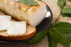 Sandwich with lard and laurel leaf. On a black plate Stock Images