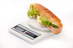Sandwich with letuce and ham on the digital scale.  Stock Photo