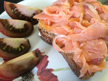 Sandwich with lox. Sandwich with smoked salmon and tomatoes on the side royalty free stock image