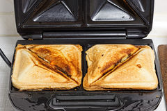 Sandwich maker. Crispy fresh toasted cheese toasts in sandwich maker Stock Photos