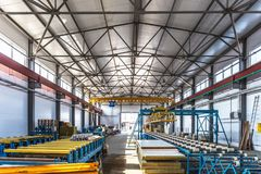 Sandwich manufactory panel production line. Equipment machine tools and roller conveyor in large hangar or workshop. Interior stock photos