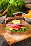 Sandwich meal. Big tasty toast sandwich with sausage on the table Stock Image