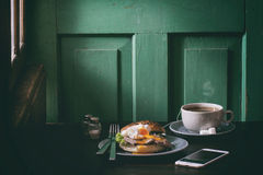 Sandwich with meat and egg. Cafe Breakfast with homemade sandwich with baked meat and soft-boiled egg and cup of hot pocket tea over dark wooden table near the Royalty Free Stock Image