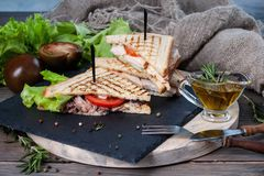Sandwich with meat and fresh vegetables on a wooden table royalty free stock photo