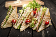 Sandwich with meat and greens and toast on a table made of wood Stock Photos