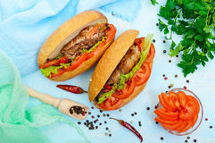 Sandwich: Meat rolls with vegetables in a bun with tomato and lettuce leaves. royalty free stock image