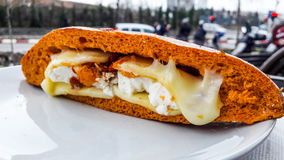 Sandwich with melted feta cheese and dried tomato in the city. orange bread Stock Photo