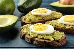 Sandwich met avocadopuree en ei op een blauwe houten lijst Close-up stock fotografie