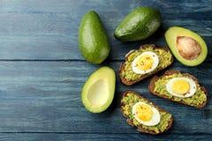 Sandwich met avocadopuree en ei op een blauwe houten lijst met ruimte voor tekst Mening van hierboven stock afbeelding