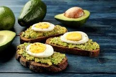 Sandwich met avocadopuree en ei op een blauwe houten lijst Verse avocado stock afbeeldingen