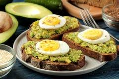 Sandwich met avocadopuree en ei op een plaat en ingrediënten voor het koken op een blauwe houten lijst stock foto's