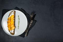 Sandwich met dadelpruim en zachte kaas op een zwarte achtergrond met ruimte voor tekst royalty-vrije stock afbeelding